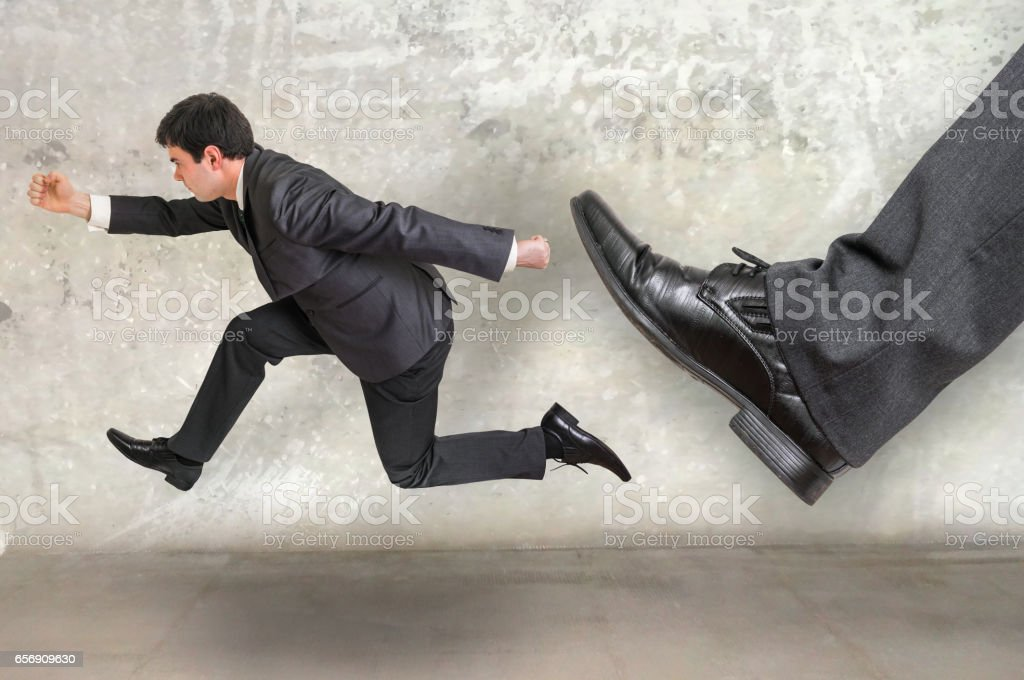 Small businessman running away from a boss pressure stock photo