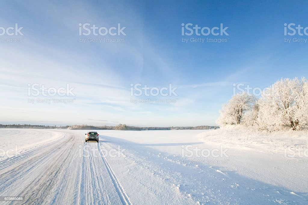 Small car driving along a snowy, icy road in winter stock photo