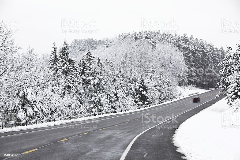 Small Car Speeding on Rural Adirondacks Highway in Blizzard stock photo