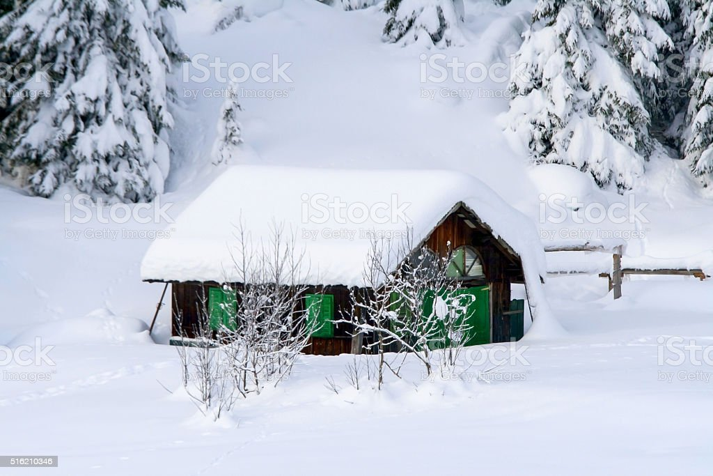 Small chalet in the snow of the dolomites stock photo