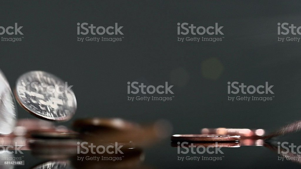 Small change falling onto dark, reflective surface. stock photo