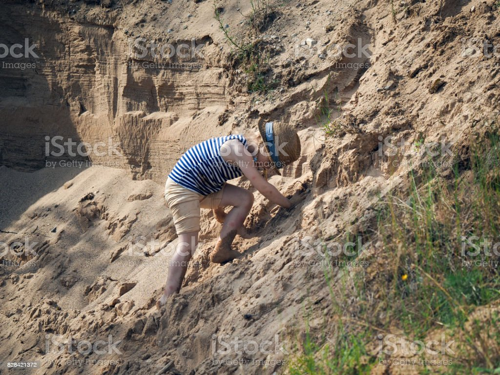 A small child climbs on sand mountain stock photo