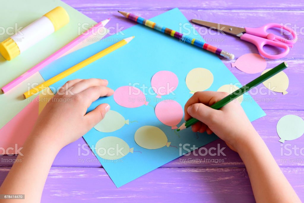 Small child doing a paper card. Child holds a pencil in hand stock photo
