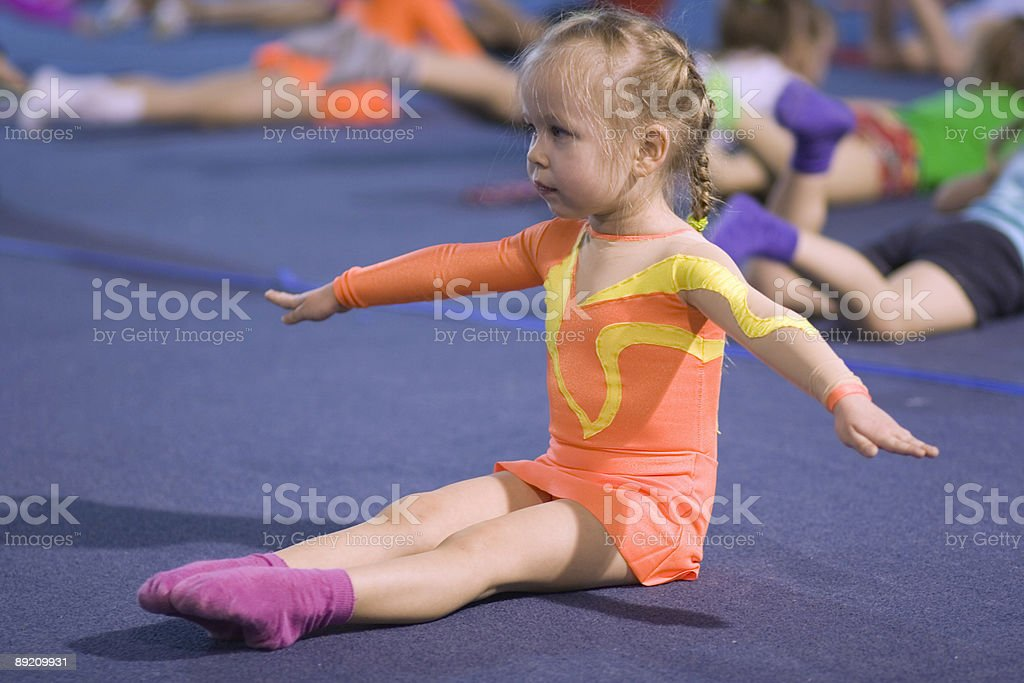 A small child gymnast following instructions royalty-free stock photo