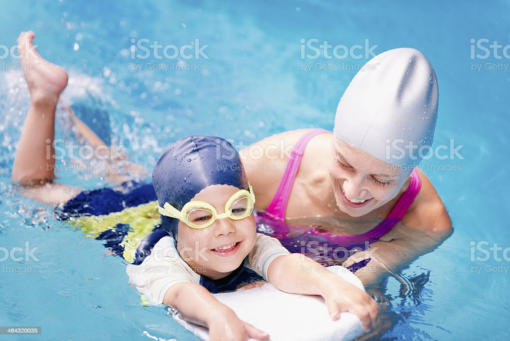 Small child holds on to swim guide in water with woman stock photo