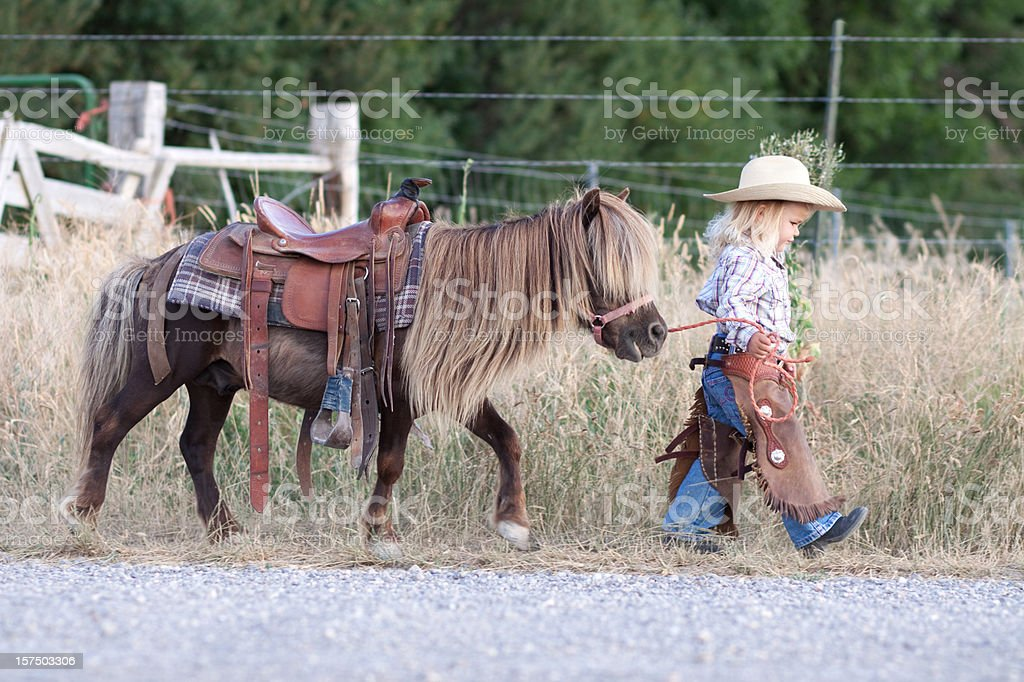 Small child in cowboy outfit with cute hairy pony on a lead stock photo