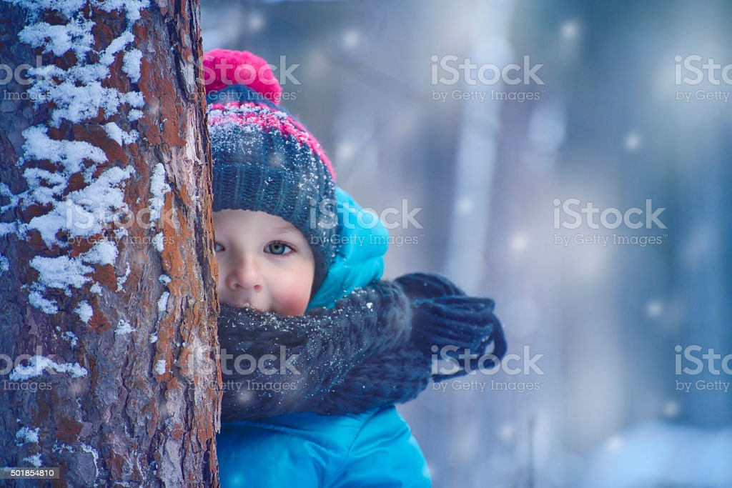 small child in the winter forest stock photo
