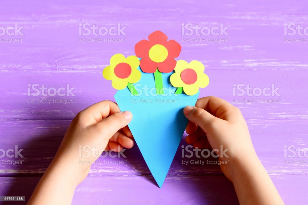 Small child made paper flowers crafts for mother's day or birthday stock photo