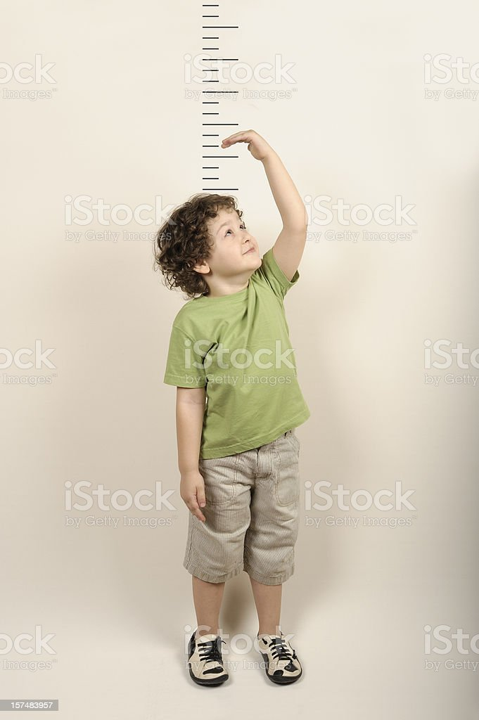 Small child measuring himself standing up stock photo
