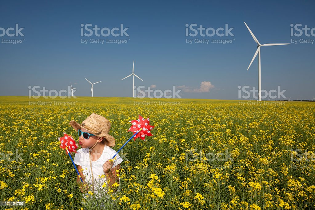 Small child playing in wildflower field with wind turbines royalty-free stock photo