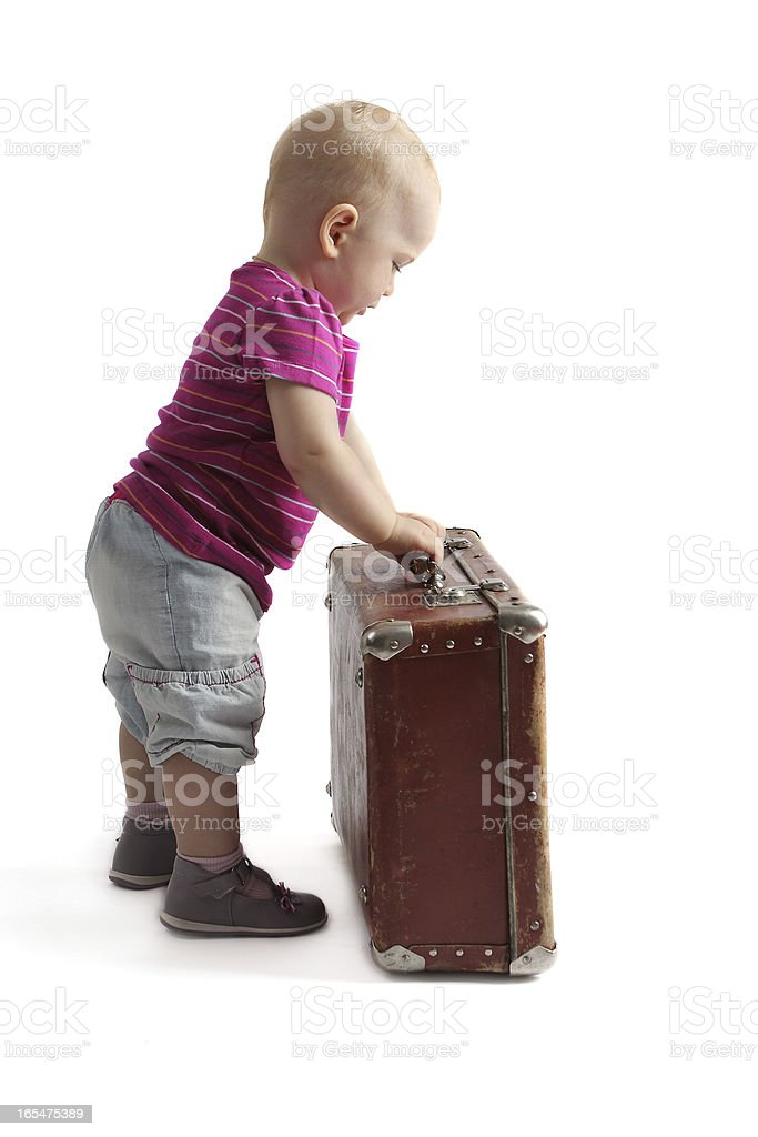 small child standing next to a suitcase, white background royalty-free stock photo