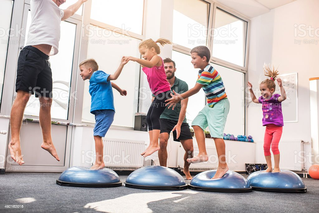 Small children jumping on bosu balls on training class. stock photo