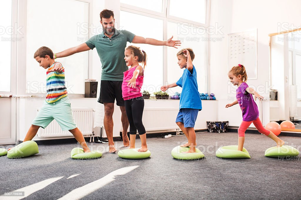 Small children walking on Pilates balls on training class. stock photo
