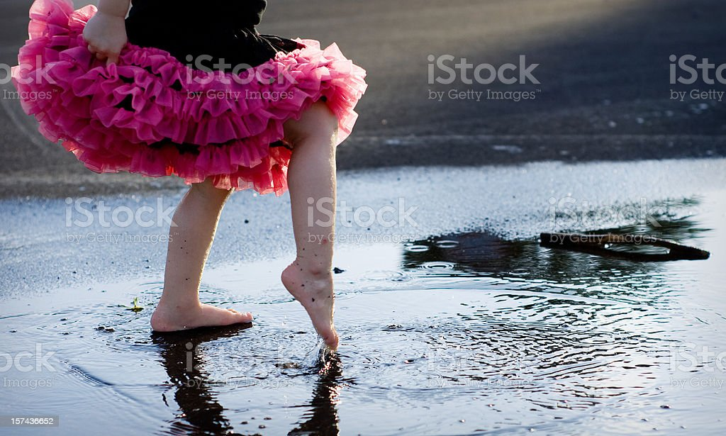 Small Child's Foot Dancing in Puddle While Wearing Tutu stock photo