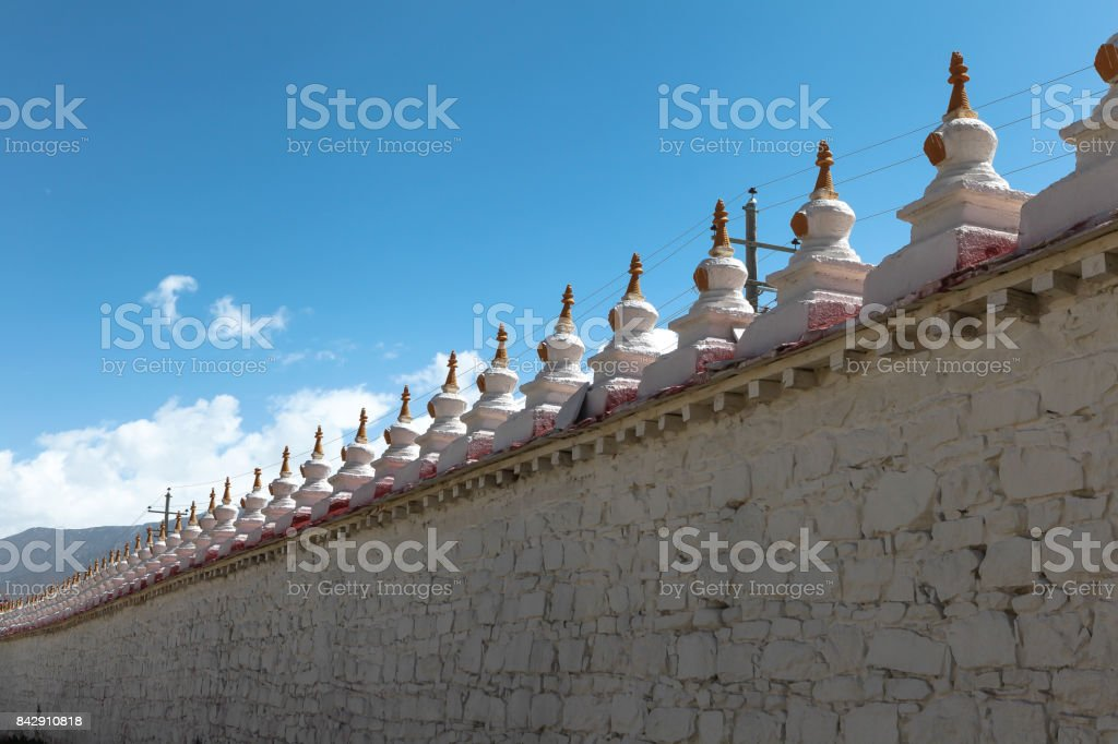 Small chortens/stupas/pagodas on the circular wall of Samye monastery,first Buddhism temple in Tibet,built based on mandala concept,represented the universe with blue sky,China stock photo