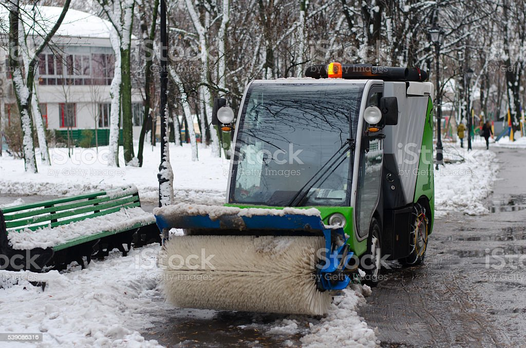 Small cleaning vehicle in the park. stock photo
