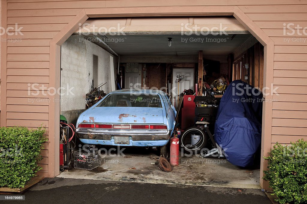 Small cluttered home garage viewed from the driveway stock photo