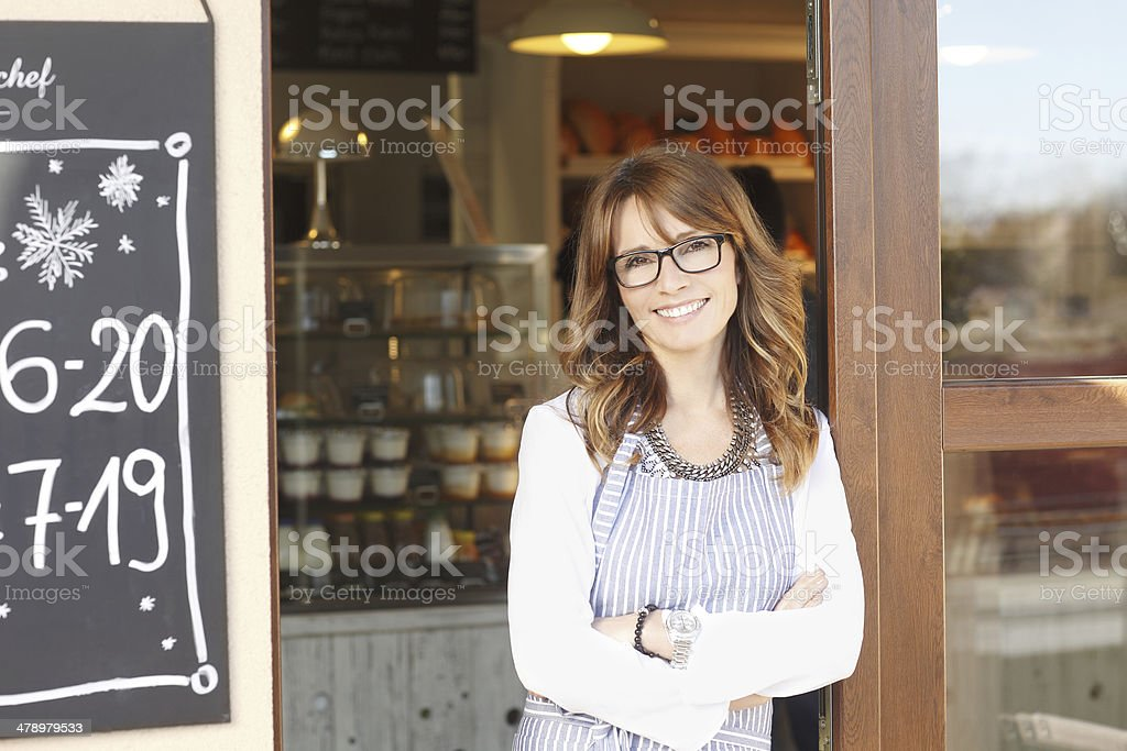 Small coffee shop owner standing in front of store. stock photo