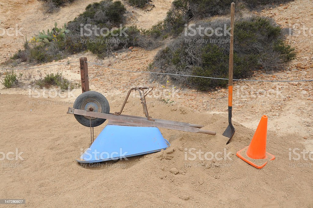Small construction site with wheelbarrow, shovel, and orange cone royalty-free stock photo