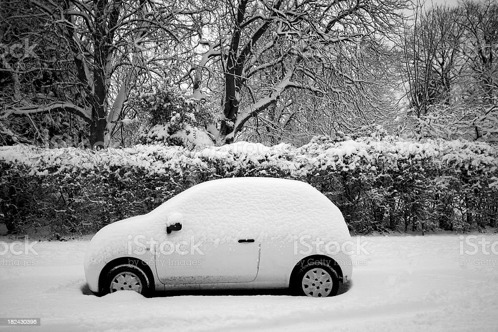Small covered  in snow parked on the street stock photo