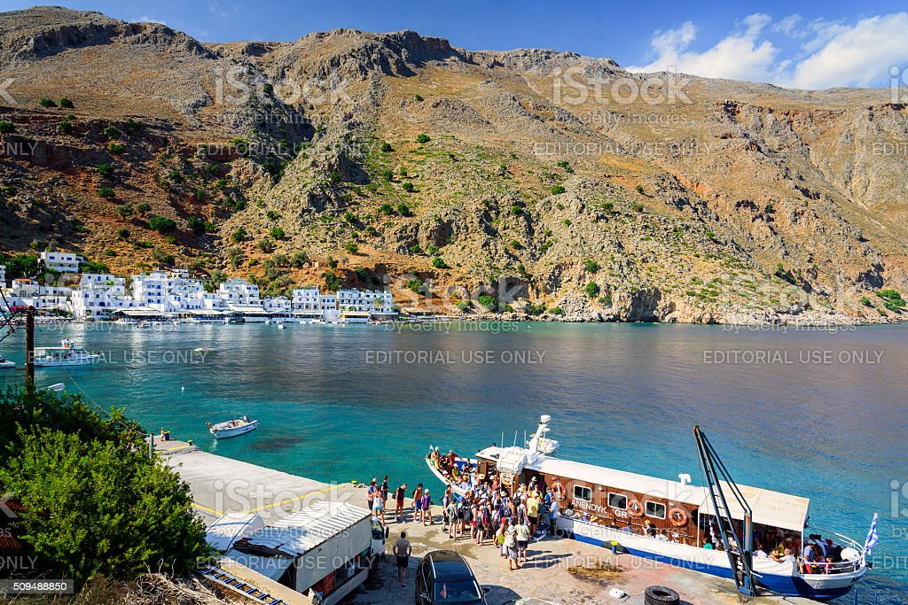 Small cruise ship unloading tourist at port of Loutro town stock photo
