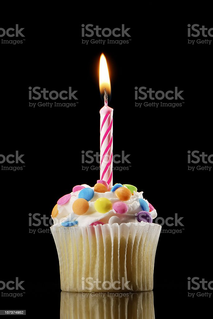 Small cupcake with colorful candy and a candle on top stock photo
