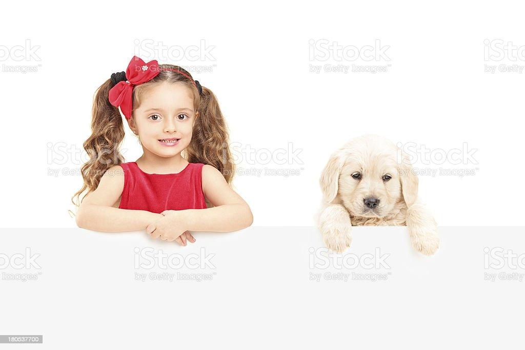 Small cute girl and labrador retriever posing behind a panel royalty-free stock photo