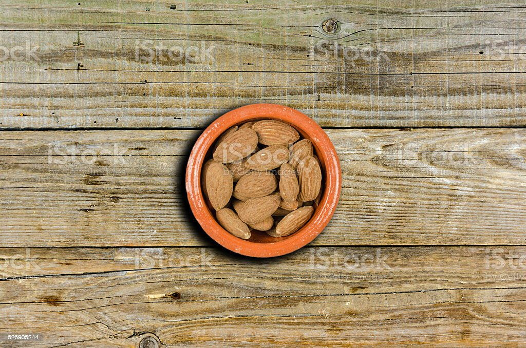 Small decorative bowl with almonds on a wooden background stock photo