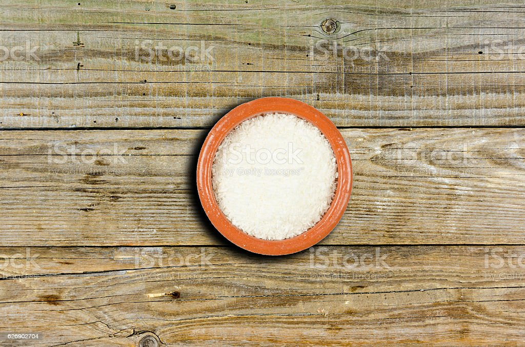 Small decorative bowl with coconut flour on wooden background stock photo