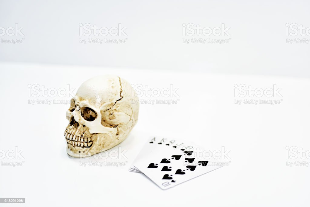 Small decorative human skull with playing cards. stock photo
