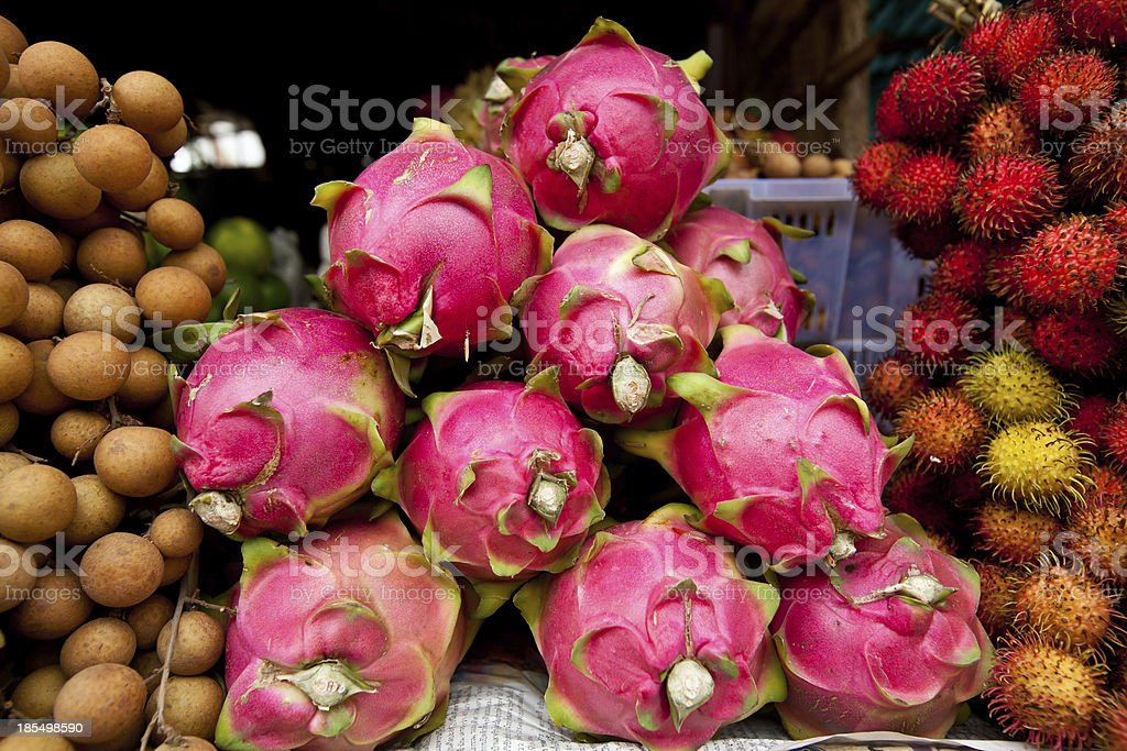 Small Dragon Fruit display next to rambutan in Cambodian Market royalty-free stock photo
