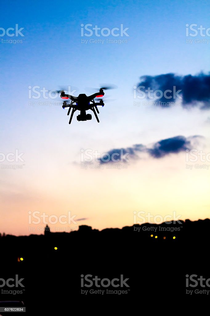 Small Drone with Camera Flies At Sunset, Skyline in Distance stock photo