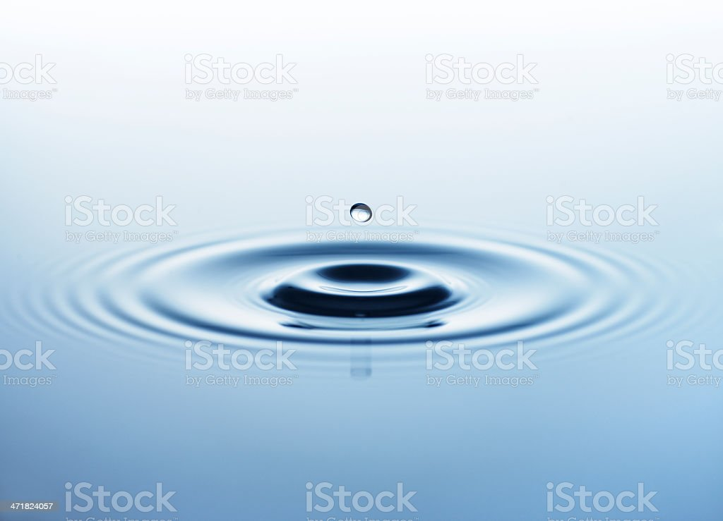 A small droplet of water making ripples through water stock photo
