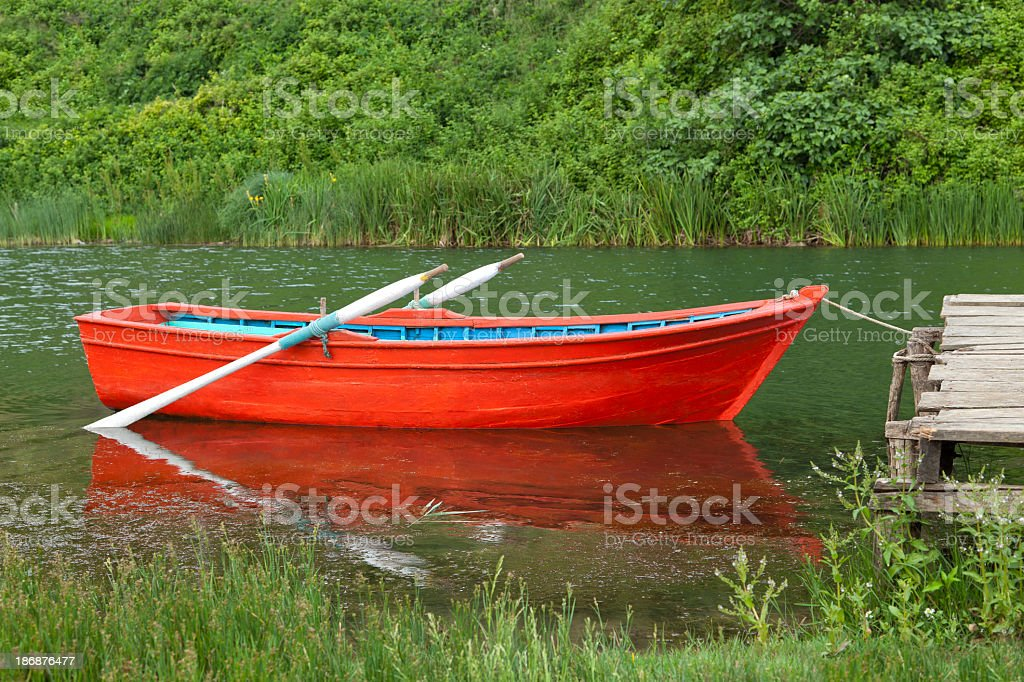 A small empty red row boat docked in a lake stock photo