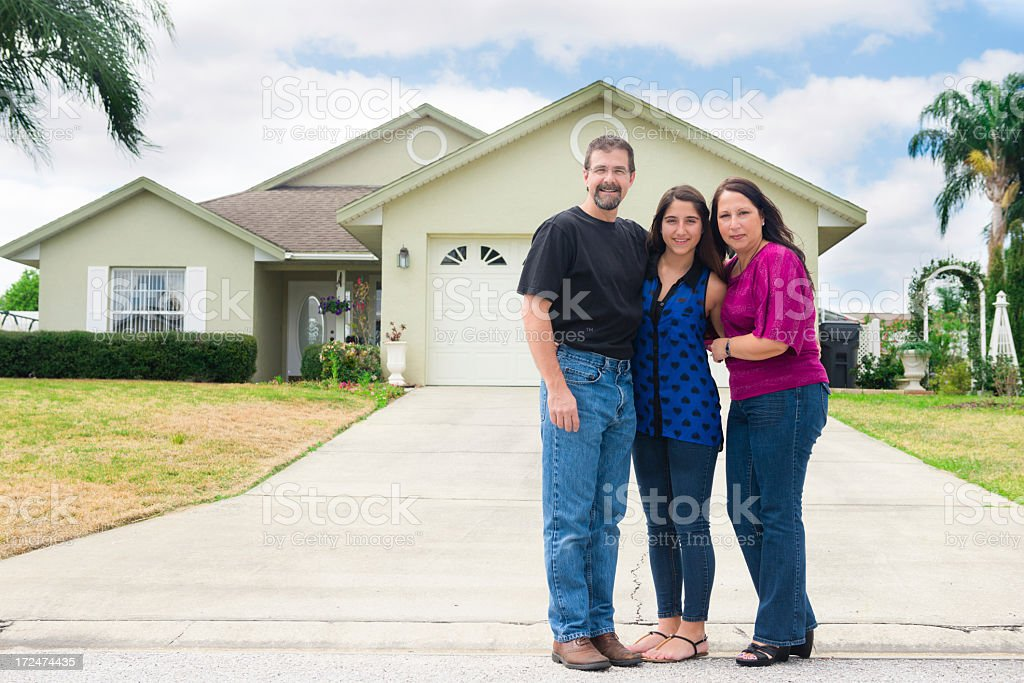 Small family poses in front of new home stock photo