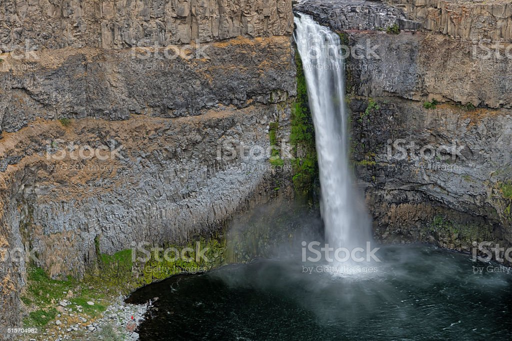 Small figures next to large Palouse Falls stock photo