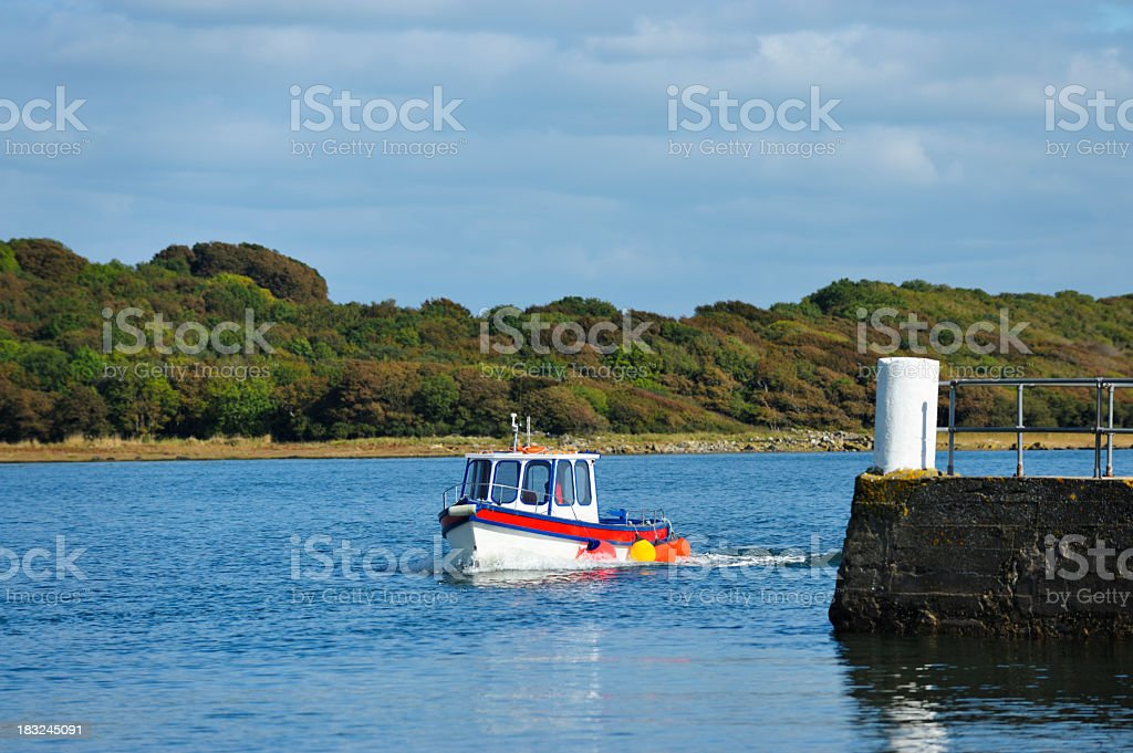 Small fishing boat coming into a Scottish harbour stock photo