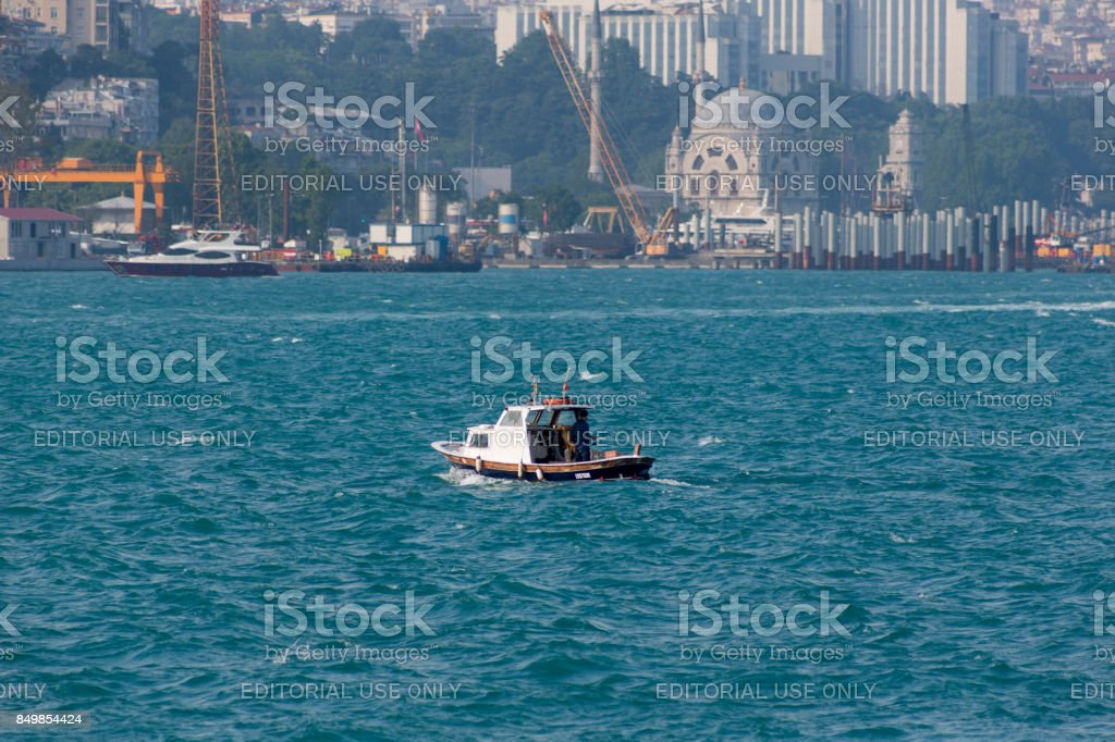 small fishing boat is travelling at bosphorus strait in istanbul turkey stock photo