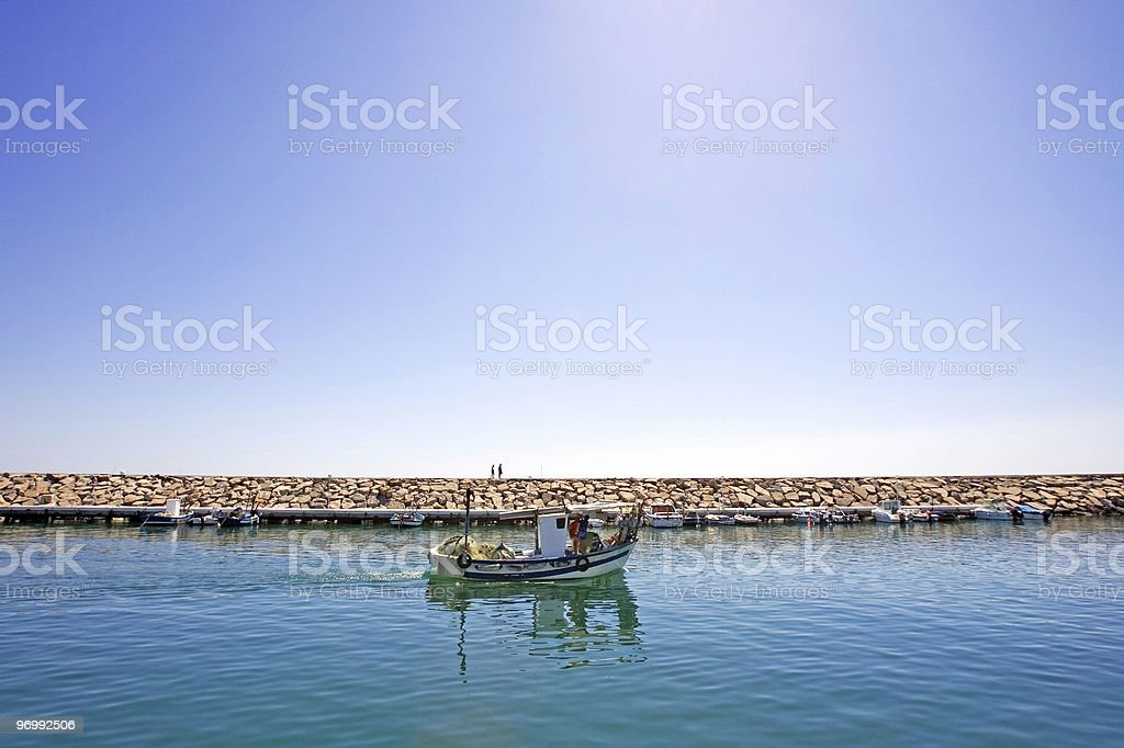 Small fishing boat leaving the port of Duquesa in Spain stock photo