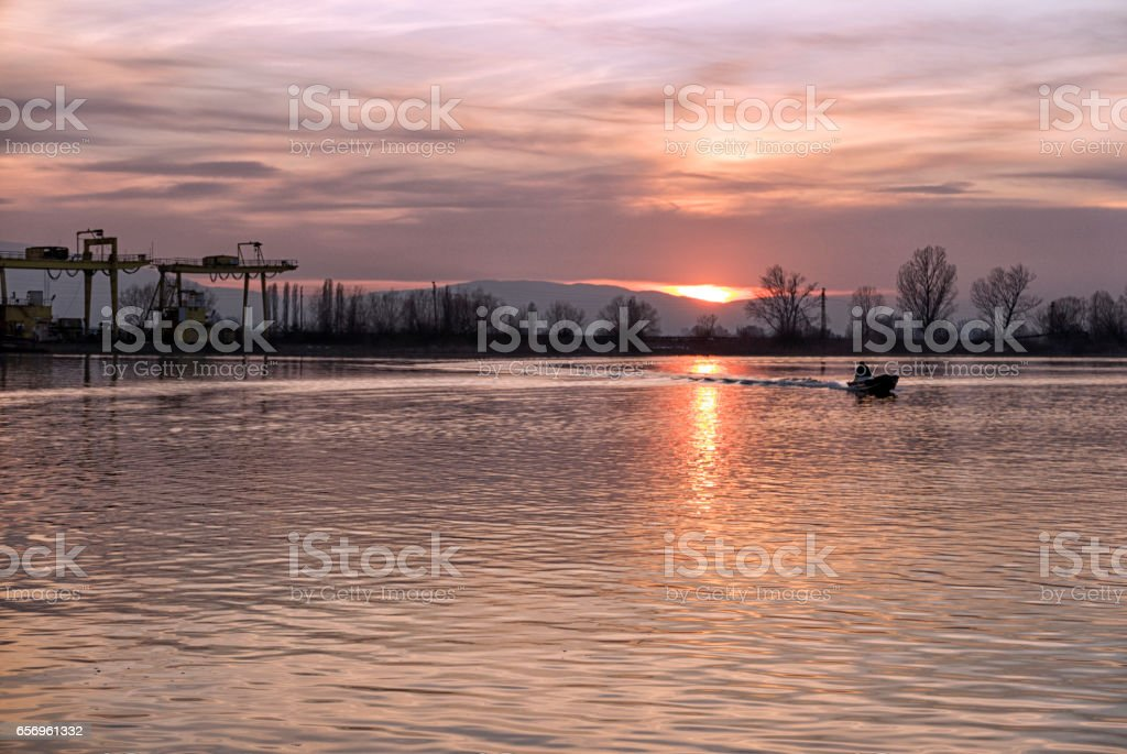 Small fishing boat on the sunset lake stock photo