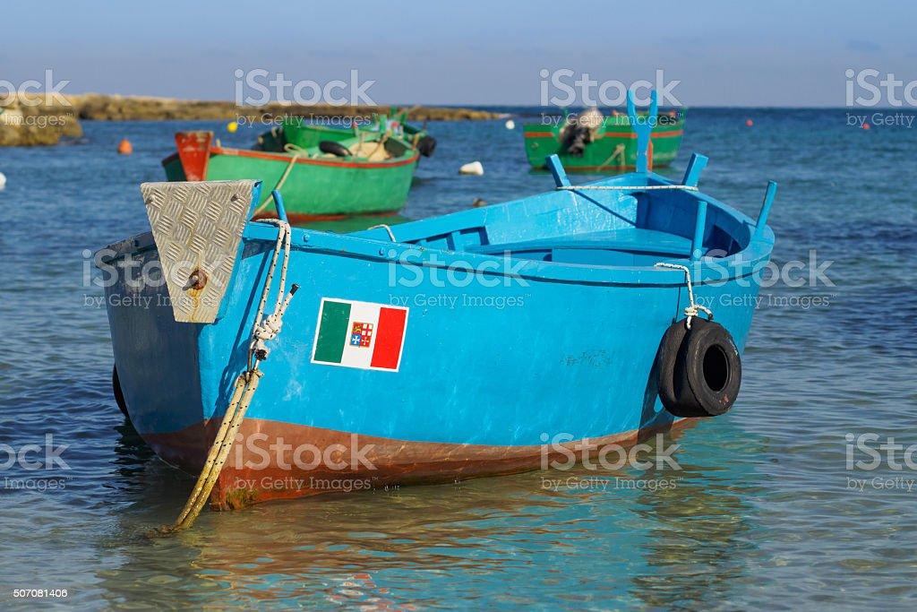 Small fishing boat with Italian flag - Polignano a Mare stock photo