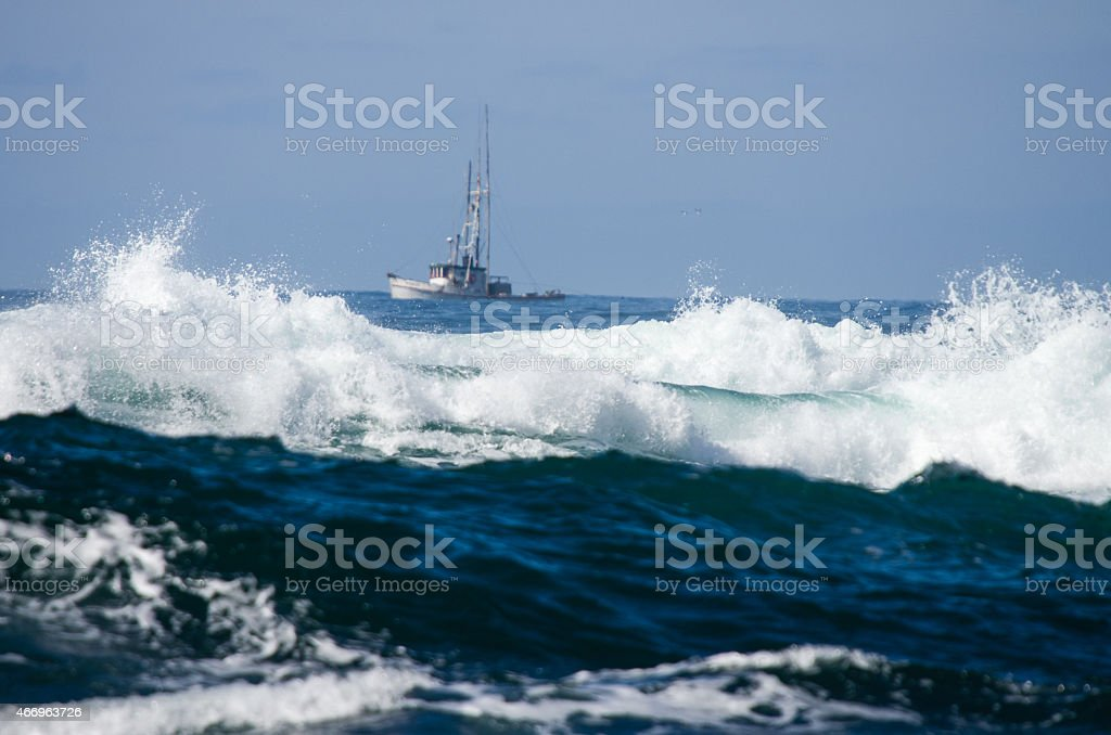Small fishing boat with surf stock photo