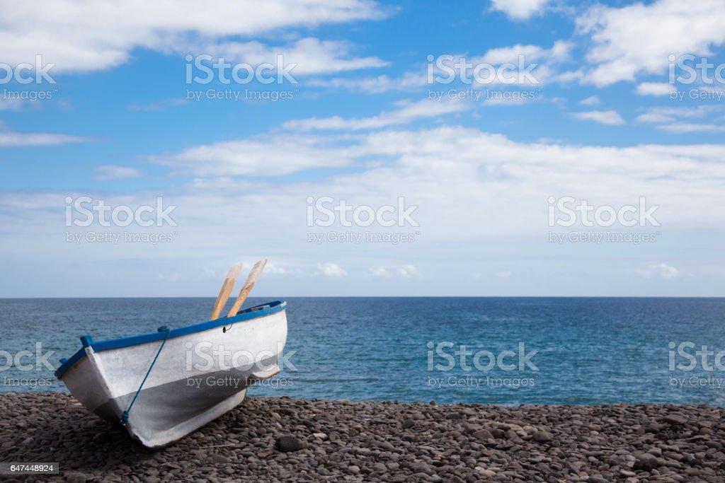 small fishing dinghy on sunny stony shingle beach Fuerteventura Canary Islands Spain stock photo