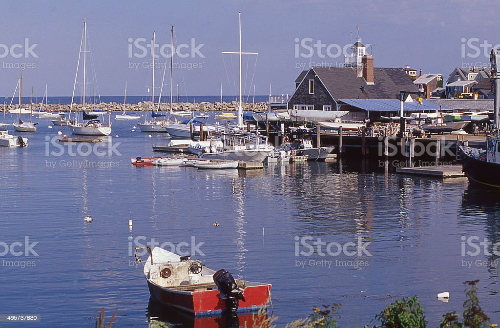 Small fishing skiff anchor breakwater with other boats Gloucester Massachusetts stock photo