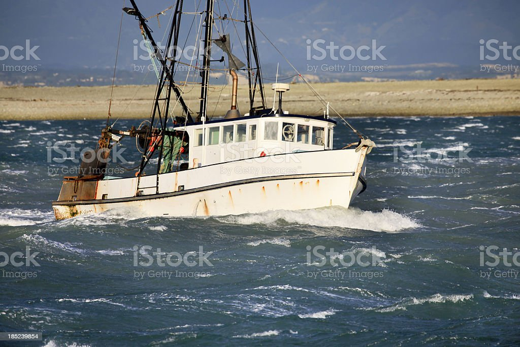 Small fishing trawler in rough seas, New Zealand stock photo