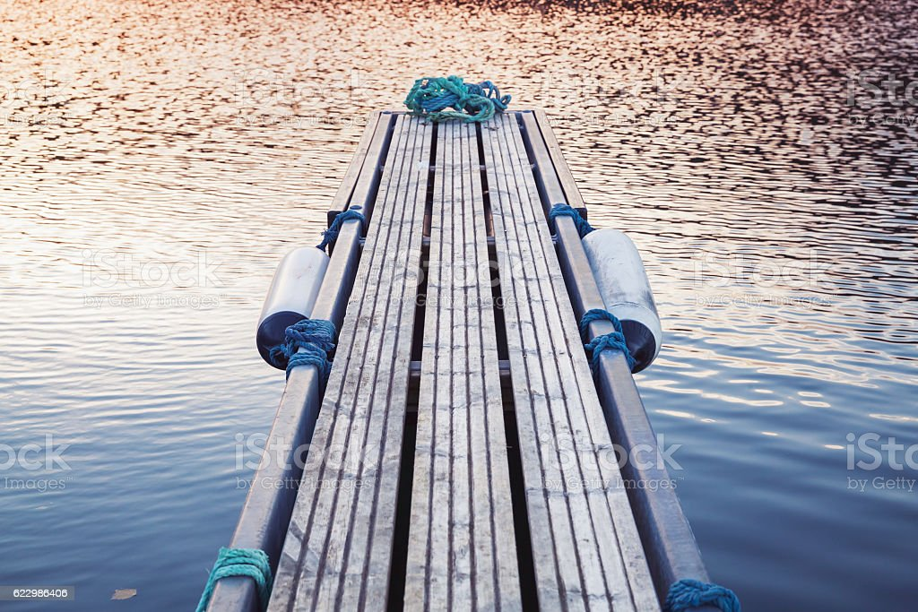 Small floating pier on still water stock photo