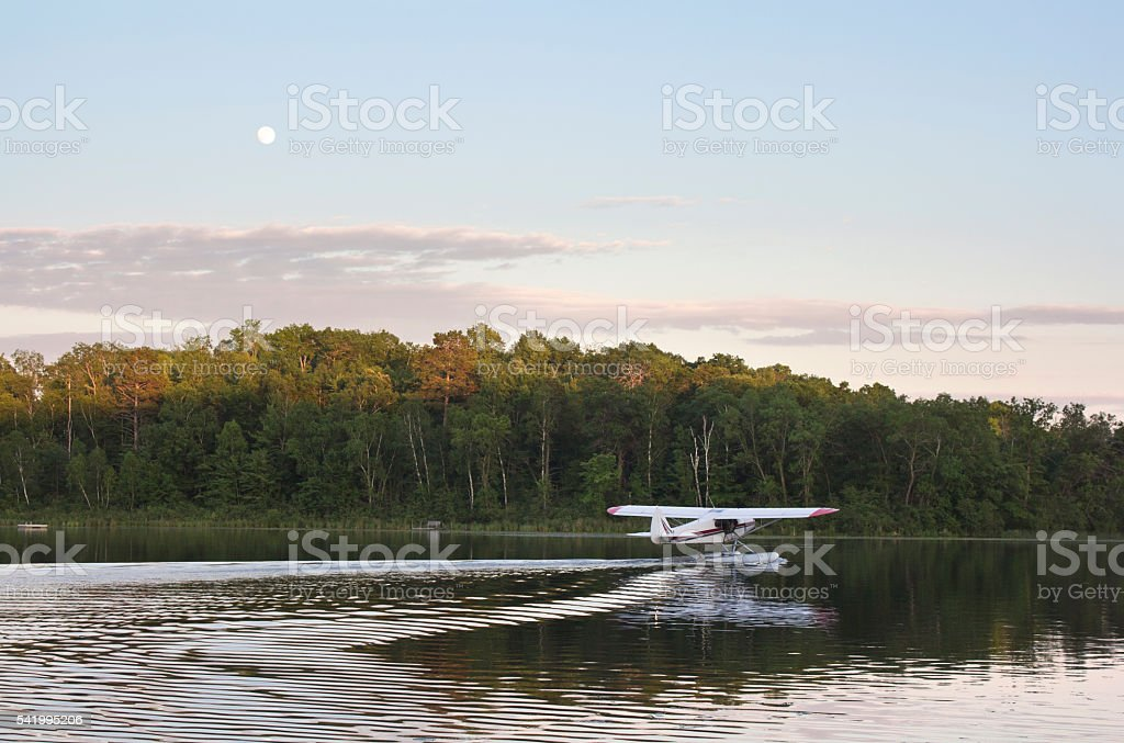 Small floatplane taxis for takeoff on calm Minnesota lake stock photo