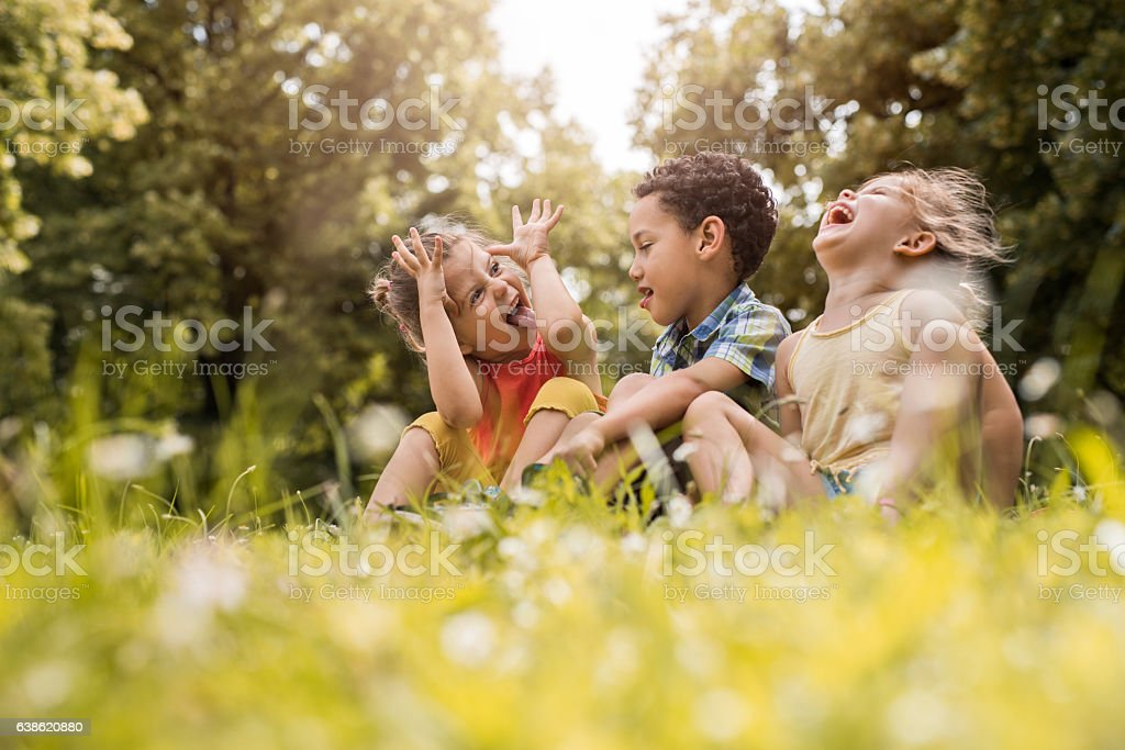 Small friends having fun while relaxing in grass. stock photo