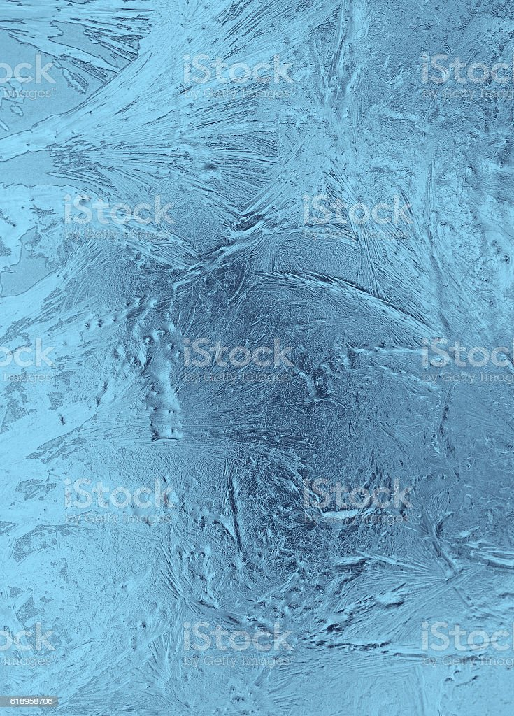 Small frosty patterns on glass in light blue tones stock photo