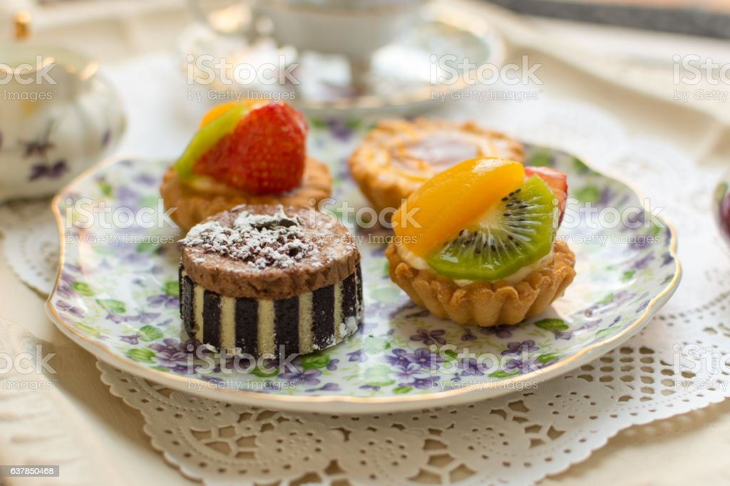 Small fruit tarts laid out on an antique china plate stock photo